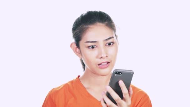 překvapený mladá žena na sobě oranžový svetr a při pohledu na její smartphone na bílém pozadí