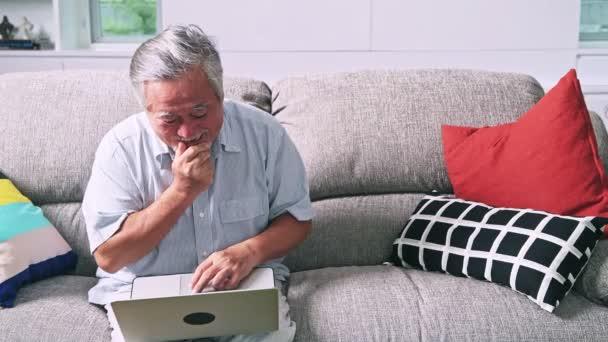 alter Mann versucht, Computer im Wohnzimmer zu benutzen. asiatischer Mann mit weißem Bart mit Laptop, aufgewühlte Stimmung. Senioren-Lebensstil-Konzept.