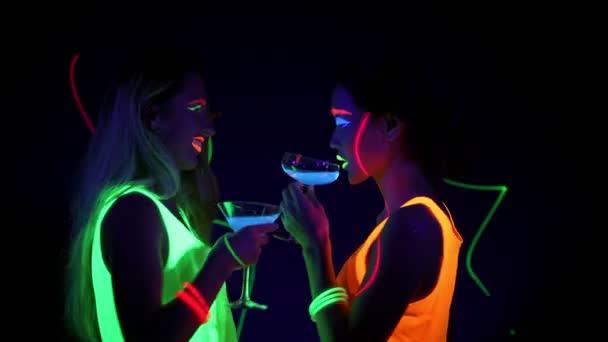 Krásné sexy ženy s Uv barvy na obličej, laser, Svítící náramky, nápoje, zářící oblečení tančí spolu před kamerou, polovina těla výstřel. Kavkazská a Asijské žena. Strany koncepce.