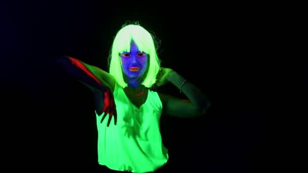 Krásná sexy žena s Uv barvy na obličej, paruka, zářící, oblečení tance před kamerou, polovinu těla výstřel. Kavkazský žena. Strany koncepce