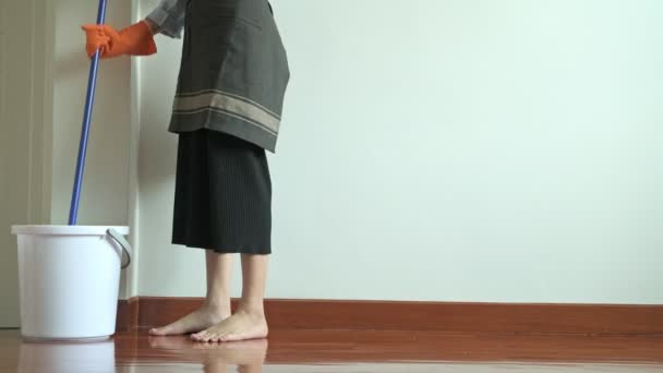Woman cleaning house with a mop. Beautiful Asian woman cleaning floor with mop. Low angle shot. House cleaning service concept.