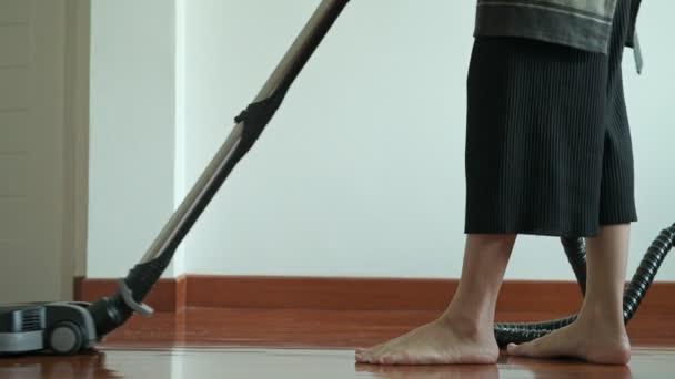 Žena, být opatrný s vysavačem. Krásná asijská žena čištění podlahy s vysavačem. Nízký úhel natočen. Dům čištění servisní koncept