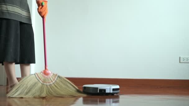 Žena, být opatrný s koštětem. Krásná asijská žena čištění podlahy s koštětem a robota. Nízký úhel natočen. Dům čištění servisní koncept