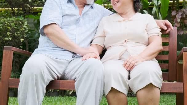 Coppie senior che si siede e parlando insieme nel giardino di casa. Pensione vecchio asiatico maschio e femmina, tenendosi per mano, felice sorriso. Concetto di lifestyle Senior.