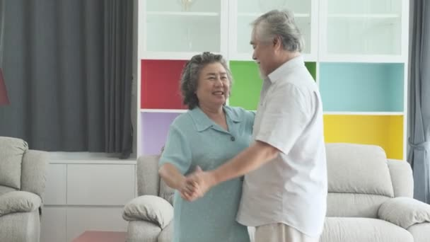 Starší pár tančí spolu v obývacím pokoji. Důchodu, staré asijské mužů a žen, tančí spolu v jejich domů, šťastný úsměv. Pojem Senior životní styl.