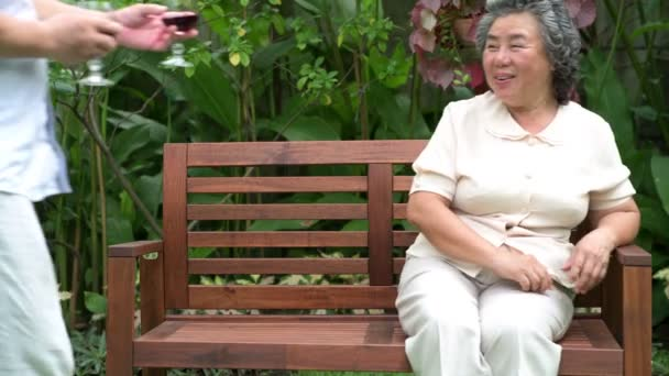 Senior couple sitting and drinking red wine together in home garden. Retired old Asian male and female, husband bring wine glass to wife, happy smile. Senior lifestyle concept.