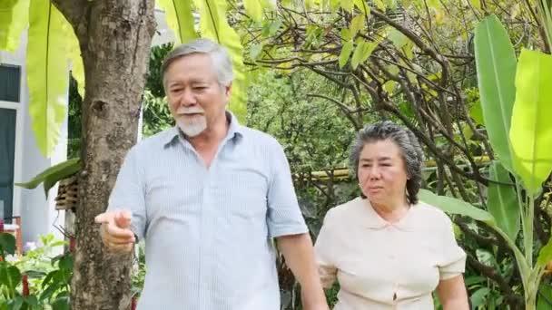 Idősebb pár ápolási otthon járkálni. Régi ázsiai férfi és női walkingtoward kamera, beszélő, boldog mosollyal. Vezető életmód fogalma.