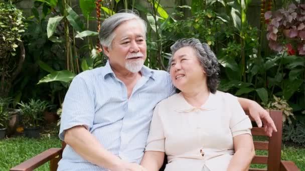 Vedoucí pár sedí a mluví spolu v domácí zahradě. Výslužbě staré asijské muži i ženy, mluví, šťastný úsměv. Pojem Senior životní styl.