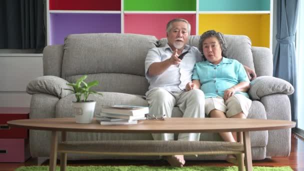 Idősebb pár ül és nézi a Tv-ban nappali. Nyugdíjas régi ázsiai férfi és női, pihentető a nappaliban kanapéval, boldog mosollyal. Vezető életmód fogalma.