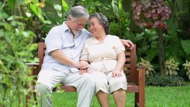 Idősebb pár ül, és beszélgettek az otthoni kertben. Nyugdíjas régi ázsiai férfi és női, beszél, boldog mosollyal. Vezető életmód fogalma.
