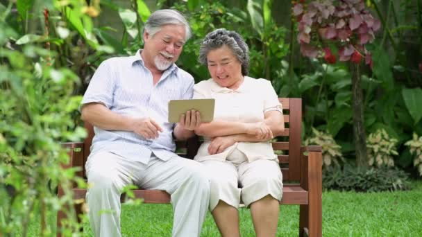 Senior couple sitting and using tablet together in home garden. Retired old Asian male and female, reading news in tablet, happy smile. Senior lifestyle concept.