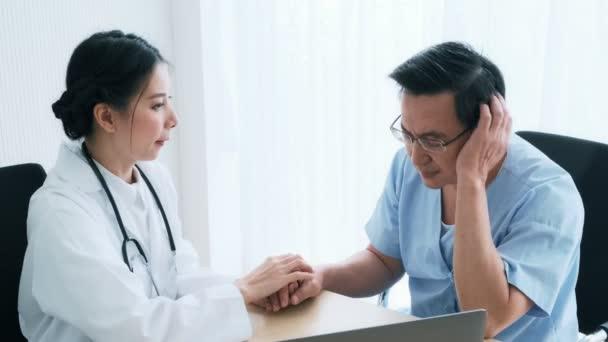 Lékař s pacientem. Mladý ženský lékař mluvil senior pacientovi v nemocnici. Sdílení výsledku lékařského testu pomocí počítače. Péče o seniory zdravotní péči a pojištění koncept.