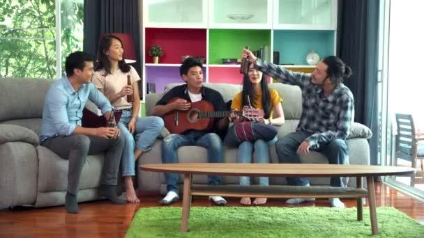 Gruppe von Freunden feiert auf Party zu Hause. Die Leute sitzen auf dem Sofa und trinken Bier. Mann spielt auf der Gitarre, während Männer und Frauen ein Lied singen