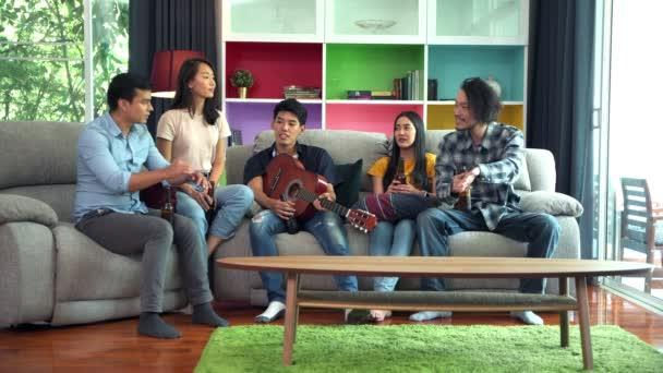 Skupina přátel oslavuje doma na večírku. Lidé sedí na pohovce a pijí pivo. Člověk hraje na kytaru a muži a ženy zpívají píseň