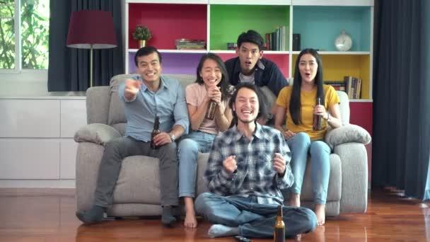 Gruppe von Freunden vor dem Fernseher zusammen auf dem Sofa. Junge Leute mit gemischter Rasse genießen es, fernzusehen, zu jubeln. Haus-Party-Konzept.