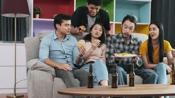 Gruppe von glücklichen Freunden feiert auf Party zu Hause. Menschen, die Pizza essen und Bier trinken