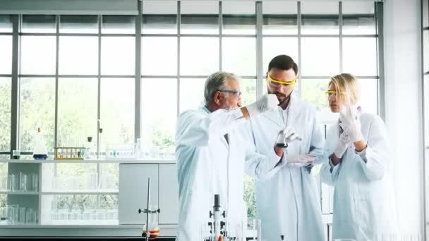 Skupina chemici pracující v laboratoři. Mladé bílé mužské a ženské chemici s hlavní Kavkazský chemik pracují společně v laboratoři, míchání chemikálií. Věda koncept
