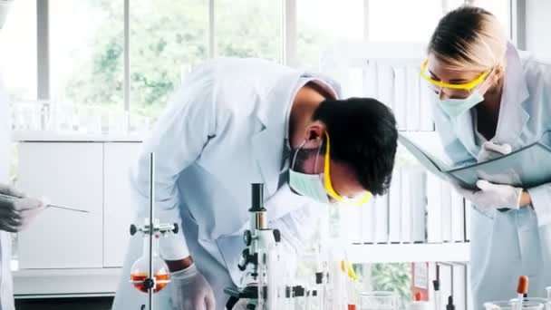 Group of chemists working in a lab. Young white male and female chemists with senior caucasian chemist working together in lab, looking into microscope. Science concept.