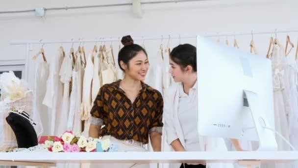 Mladý módní návrhář domu pracují společně. Svatební šaty, mladá asijská žena s počítačem, přičemž zákazníci objednávky. Malé obchodní koncept.