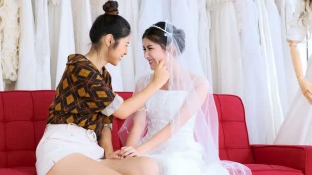 Ázsiai leszbikus pár ruha menyasszony piros kanapén ül. Megható egymást. LMBT-koncepció.