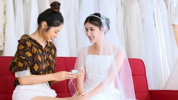 asiatisches lesbisches Paar auf rotem Sofa im Brautkleid. ein überraschendes Geschenk, spannend und überraschend aussehen. lgbt-Konzept.