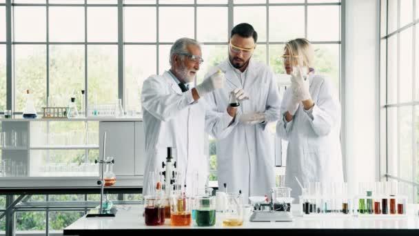Csoport kémikusok munka egy laborban. Fiatal fehér férfi és női vegyészek vezető kaukázusi kémikus együtt dolgoznak a laborban, keverés vegyi anyagok. Tudomány fogalom.