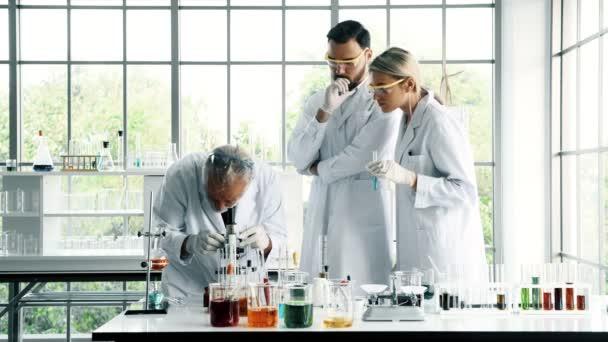 Csoport kémikusok munka egy laborban. Fiatal fehér férfi és női vegyészek vezető kaukázusi kémikus együtt dolgoznak a laborban, látszó-ba Mikroszkóp. Tudomány fogalom.