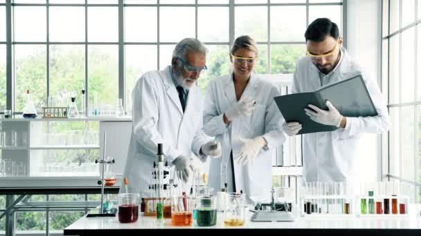 Csoport kémikusok munka egy laborban. Fiatal fehér férfi és női vegyészek vezető kaukázusi kémikus együtt dolgoznak a laborban, beszélünk a munka. Tudomány fogalom.