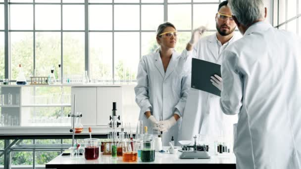 Group of chemists working in a lab. Young white male and female chemists with senior caucasian chemist working together in lab, taking notes. Science concept.