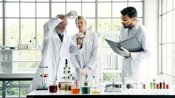 Csoport kémikusok munka egy laborban. Fiatal fehér férfi és női vegyészek vezető kaukázusi kémikus együtt dolgoznak a laborban, jegyzeteket. Tudomány fogalom.