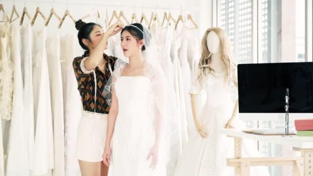 Mladí svatební šaty značkové pracovní. Mladá asijská žena nechat její zákazník vyzkoušet na nové svatební šaty. Malé obchodní koncept.