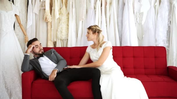 Romantic wedding couple in expensive dress shop. White man and woman in bride dress, woman gently wake his man up in sofa. Romantic young couple concept.