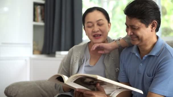Starší asijské muž čte knihu s jeho krásnou ženou v obývacím pokoji. Koncepce důchodového Senior životní styl.