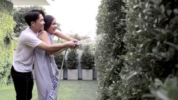Young asian couple watering plants in their roof top garden. Slow motion shot.