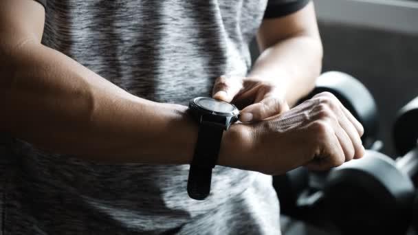 Seniorchef mit Smartwatch im Fitnessstudio.