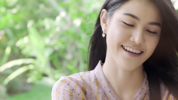 Super pomalý pohyb asijské ženy na portrétu ve své domácí zahradě se zeleným stromem v pozadí, s prostorem pro kopírování. Koncepce životního stylu tisíciletí.