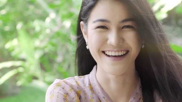Super Slow motion of millennial generation Asian woman smile at camera portrait in her home garden with green tree in background, with copy space. Millennial lifestyle concept.