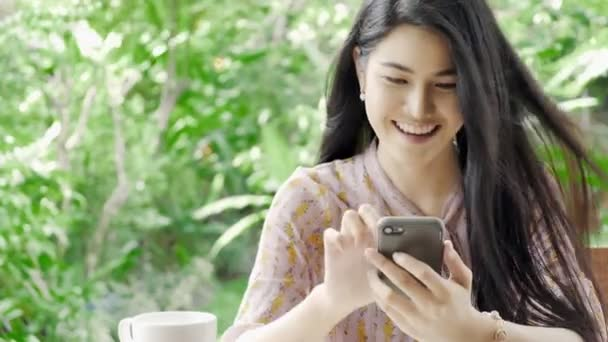 Young beautiful Asian woman browsing her phone with smile at her home garden with green tree in background. Millennial lifestyle and social connection concept.