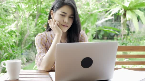 Young attractive asian woman working on laptop at her home garden with green tree in background, confusion mood. Millennial freelancer lifestyle concept.