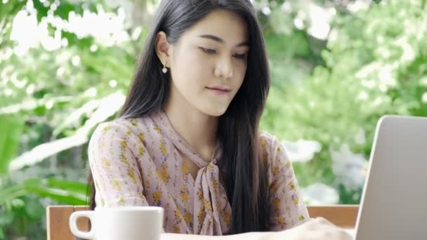 Young attractive asian woman typing email at her laptop at her home garden with green tree in background, close up shot. Millennial business woman lifestyle concept.