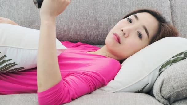 Young attractive asian woman laying on couch at home using television remote control, switching channel. Lazy and relax mood. Lonely woman life style concept.