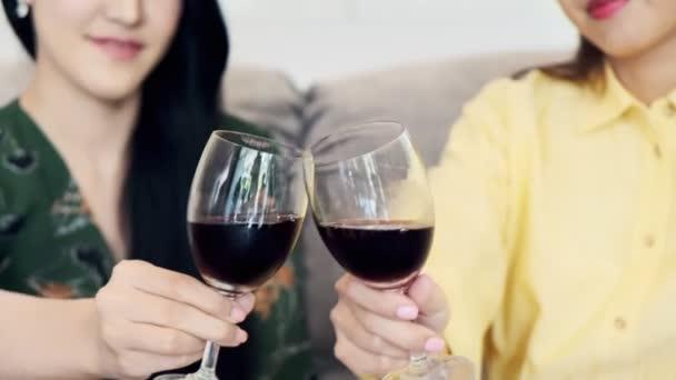 junge asiatische Frauen sitzen auf der Couch, prosten Rotweinglas zu und trinken zusammen im Wohnzimmer zu Hause, glückliches Lächeln. Konzept der Freundschaftsbeziehung.
