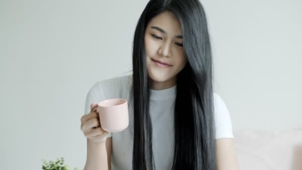 Young beautiful asian woman sitting in bed holding coffee cup and smile. Young woman relaxation lifestyle concept.