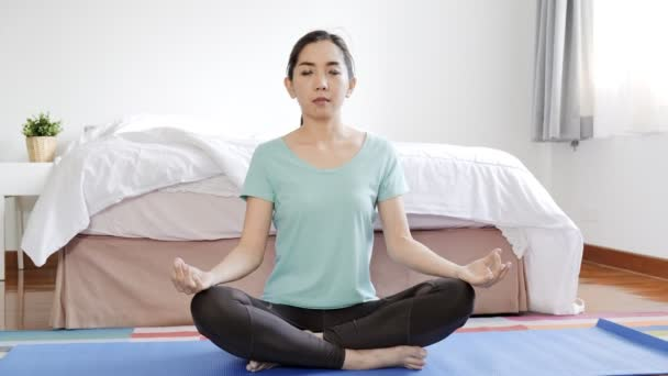 Young beautiful asian woman practice yoga at home. Relaxing home concept.