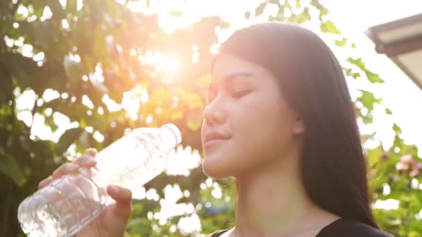 Slow motion of young beautiful asian woman holding water bottle and about to drink. Sport concept.