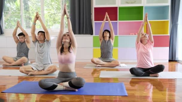 Skupina mladých a vyšších asijských lidí navštěvující jóga. Skupinový styl sportu.