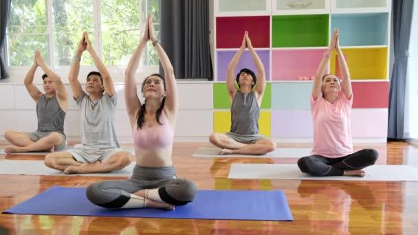 Csoport fiatal és idősebb ázsiai emberek jóga osztály, ülve le üzembe karját. Csoportos sportéletmód.