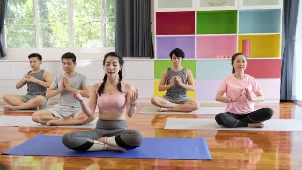 Skupina mladých a vyšších asijských lidí navštěvující jóga, kteří si sedí na meditaci. Skupinový styl sportu.