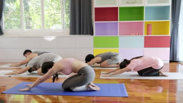 Skupina mladých a vyšších asijských lidí navštěvující jóga, roztahuje jejich záda a vtáhne se. Skupinový styl sportu.