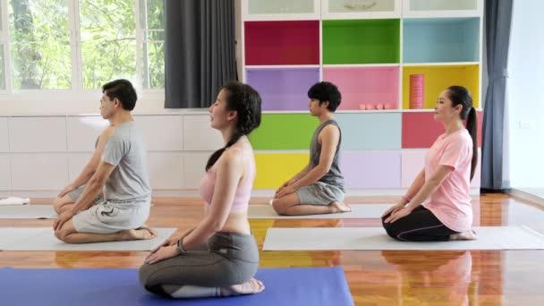 Skupina mladých a vyšších asijských lidí, kteří navštěvuje jóga, sedí a dýchá. Skupinový styl sportu.
